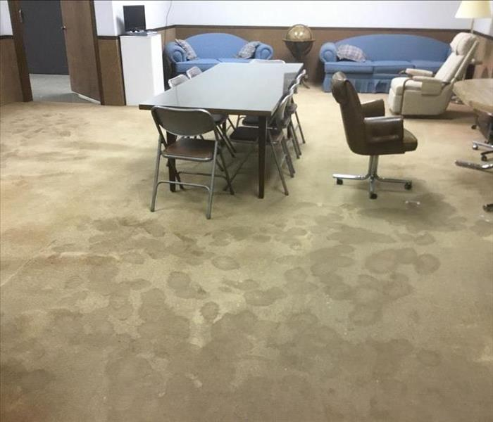 Very wet carpet in an office with footprints everywhere