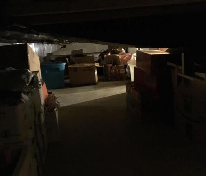 Crawl space with dry floor and boxes organized.