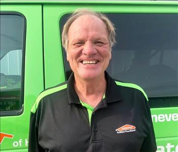 male owner of business standing in front of Green SERVPRO vehicle