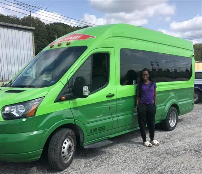 Rayanna, a production technician, standing front of SERVPRO transit van